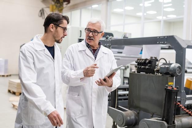 Senior en jonge kwaliteitsexperts in laboratoriumjassen met behulp van tablet tijdens het controleren van afdrukapparatuur in de drukkerij