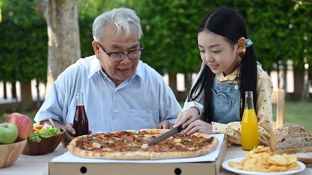 Senior en kleindochter met pizza in de tuin thuis. pensioenleeftijd levensstijl met familie op zomervakantie.