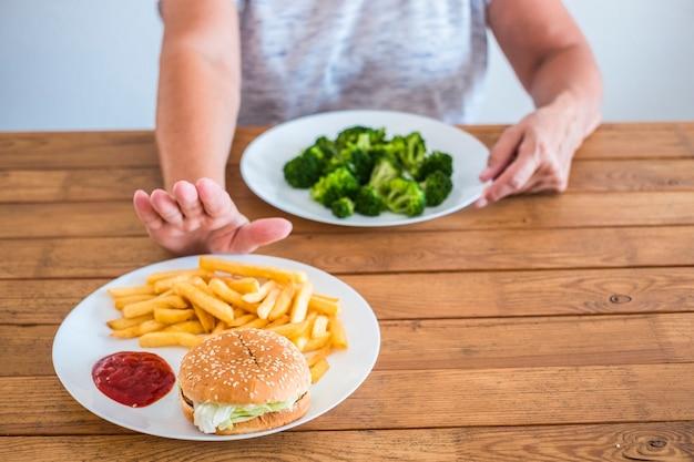 Senior en volwassen vrouw die broccoli kiest en geen hamburger - gezond en dieet levensstijlconcept om af te vallen of gezonder en goed met zichzelf te zijn