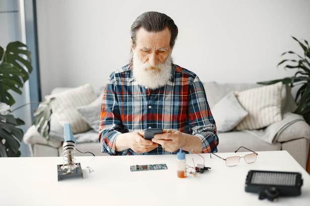 Senior engineer controleer telefoon na reparatie. herstel van gadgets.