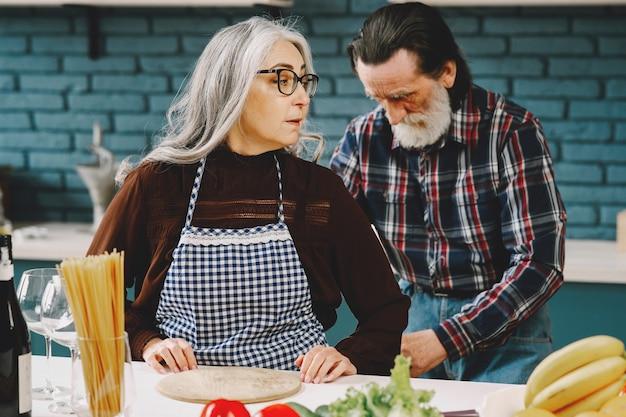 Senior europees koppel dat schorten aandoet in de keuken