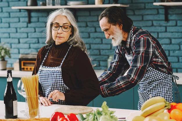 Senior europees racepaar dat schorten opdoet in de keuken