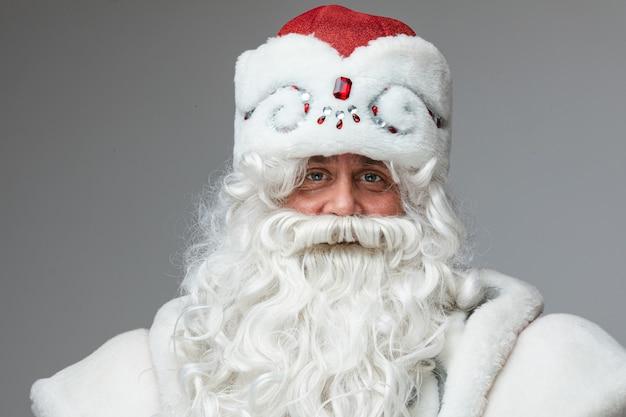 Senior father frost met versierde wintermuts en witte lange baard die naar de camera kijkt en lacht met zijn vriendelijke ogen.