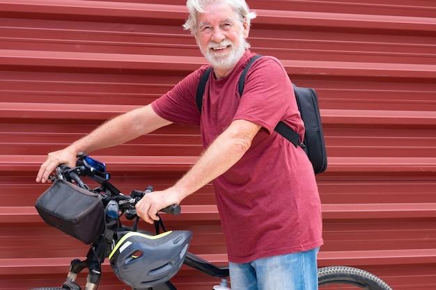 Senior fietser in excursie met zijn fiets rustend tegen een rood metalen paneel kijkend naar de camera