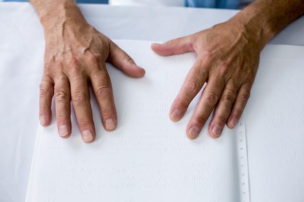 Senior gebruikt braille om te lezen