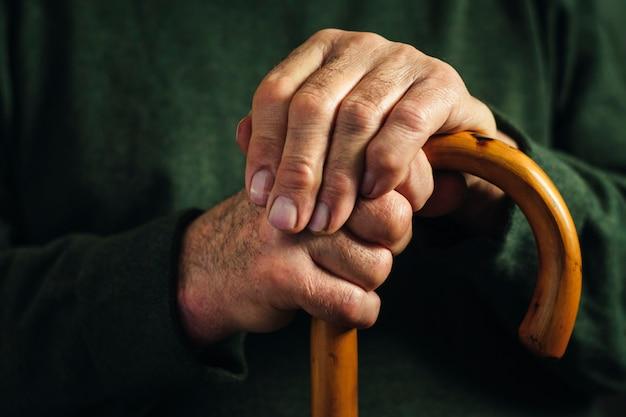 Senior gehandicapte man omklemde zijn wandelstok