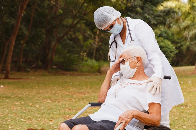 Senior gehandicapte vrouw met verzorger in de tuin van het verpleeghuis