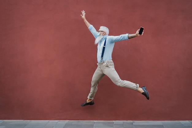 Senior gekke man buiten springen terwijl het dragen van een masker met rode muur