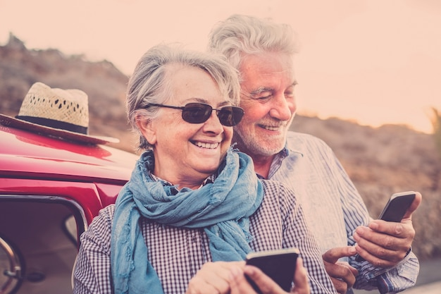 Senior gelukkig vrolijk oud kaukasisch paar gebruiken samen moderne online technologie slimme telefoon om inhoud op het web te delen en te verzenden