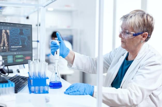 Senior genetische onderzoeker die een monster neemt uit een glazen kolf met behulp van een moleculaire dispenser. mensen in innovatief farmaceutisch laboratorium met moderne medische apparatuur voor genetisch onderzoek.