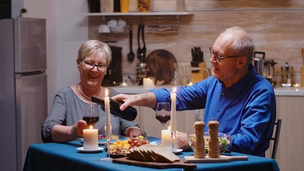 Senior gepensioneerd echtpaar dat plezier heeft met het drinken en eten van een gezonde maaltijd tijdens een romantisch diner in de keuken om hun jubileum te vieren. rijpe man en vrouwenvrouw op actief bejaarde festiviteit.