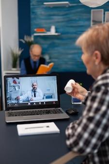 Senior gepensioneerde luisteren arts praten over behandeling tijdens online consultatie. oudere vrouw in gesprek met zorgverlener tijdens telegesprek en echtgenoot leest een boek uit