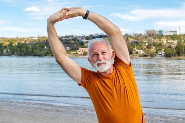 Senior gepensioneerde man die zich uitstrekt op het strand.