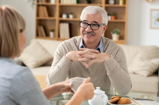 Senior gepensioneerde man kijken naar zijn dochter met een glimlach tijdens een gesprek met een kopje thee zittend aan tafel in de woonkamer