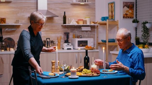 Senior gepensioneerde volwassen vrouw die diner serveert in de eetkamer. oud stel praten, aan tafel zitten in de keuken, genieten van de maaltijd, hun jubileum vieren met gezond eten.