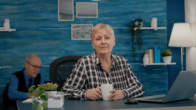 Senior gerichte vrouw kijkt naar camera zittend op de werkplek aan het bureau die vanuit huis werkt terwijl de oude vrouw tv kijkt op de achtergrond. gepensioneerde zakenman voorbereid op online vergadering met moderne gadgets