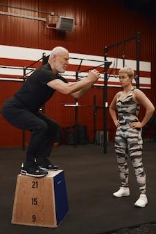 Senior gespierde mannelijke gepensioneerde m / v met grijze baard doet squats op houten kist in de sportschool terwijl zijn aantrekkelijke vrouwelijke coach naast hem staan en kijken.
