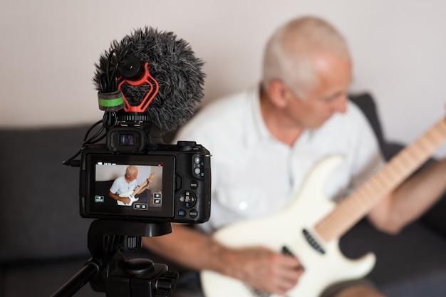 Senior gitarist die een video van zichzelf opneemt tijdens het spelen van een elektrische gitaar in de thuisstudio
