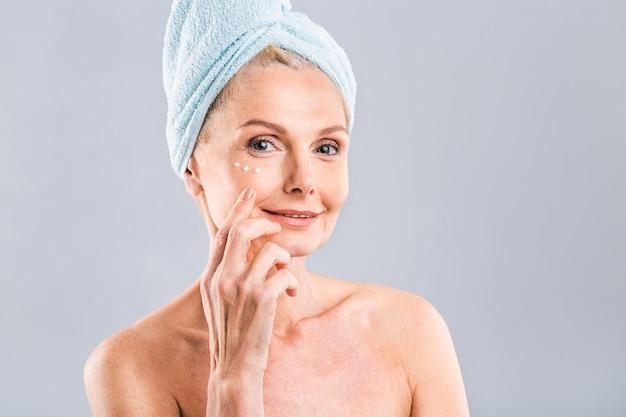 Senior glimlachen jaren 50 rijpe oudere vrouw van middelbare leeftijd die gezichtscrème op het gezicht aanbrengt en naar de camera kijkt anti-leeftijd gezonde droge huidverzorging schoonheidstherapie concept oude huidverzorgingsbehandeling