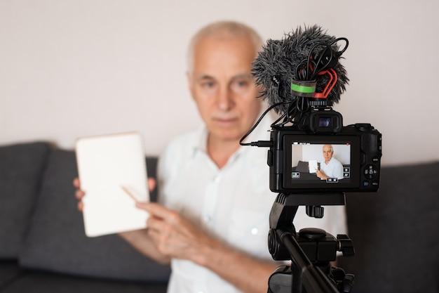 Senior grijsgehoorde professor die een video maakt voor een lezing thuis