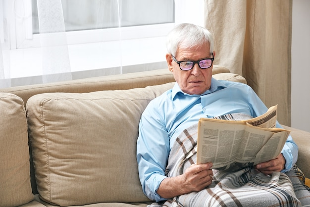 Senior grijsharige man gewikkeld in geruite krant lezen terwijl u ontspant op de bank bij het raam terwijl hij thuis blijft