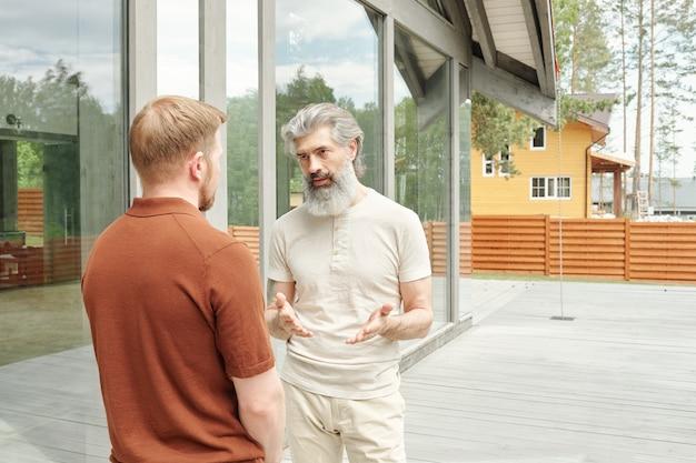 Senior grijsharige vader staande veranda van cottage huis en gebaren handen tijdens het praten met volwassen zoon