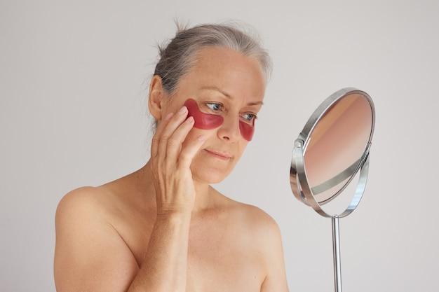 Senior grijsharige vrouw draagt ooglapjes terwijl ze in de spiegel kijkt