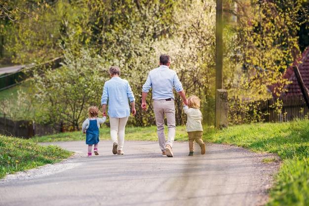 Senior grootouders met peuter kleinkinderen lopen op de weg in het voorjaar, hand in hand.