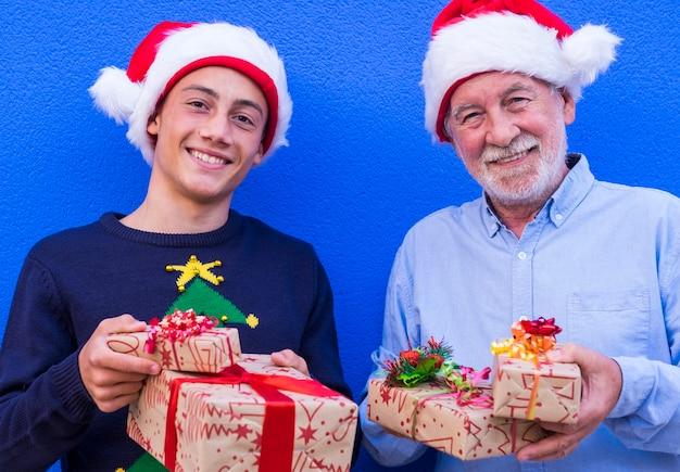 Senior grootvader en geweldige tiener kleinzoon die kerstcadeaus aanbieden met kerstmutsen