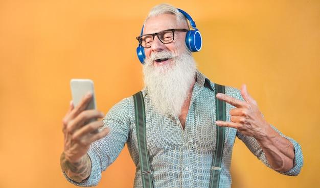 Senior hipster man die smartphone-app gebruikt voor het maken van een afspeellijst met rockmuziek - trendy tattoo-man die plezier heeft met mobiele telefoontechnologie - tech en vreugdevolle levensstijl voor ouderen - focus op gezicht