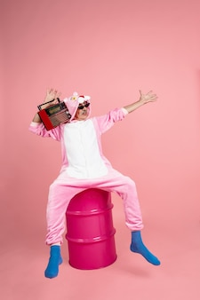 Senior hipster man in stijlvolle roze kleding geïsoleerd op roze achtergrond tech en vrolijk