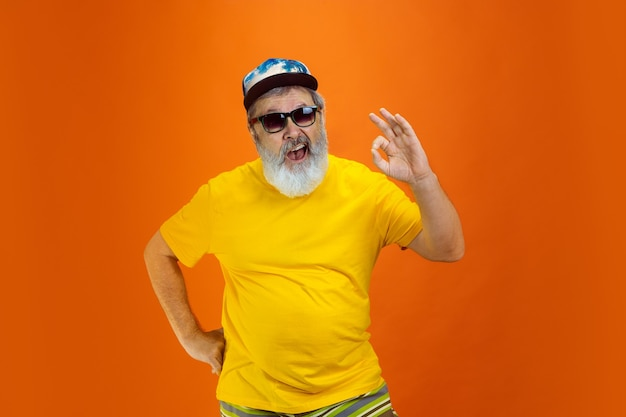 Senior hipster man met apparaten, gadgets op oranje achtergrond