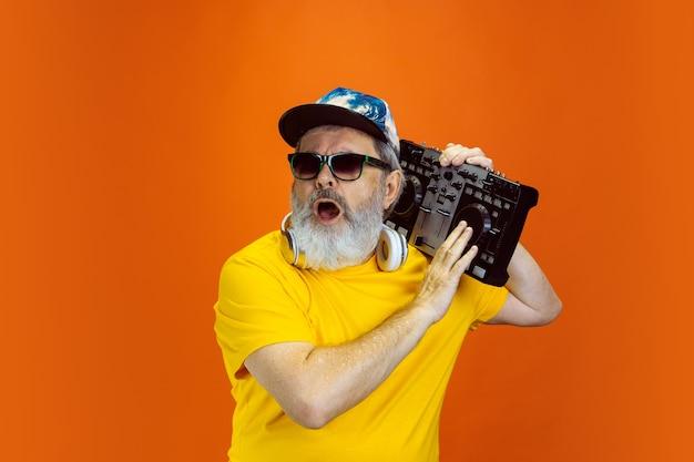 Senior hipster man met behulp van apparaten, gadgets op oranje achtergrond.