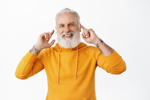 Senior hipster man met tatoeages luistert naar muziek in draadloze oortelefoons, raakt zijn koptelefoon in de oren aan en glimlacht tevreden, geniet van geweldig geluid van oordopjes, witte muur