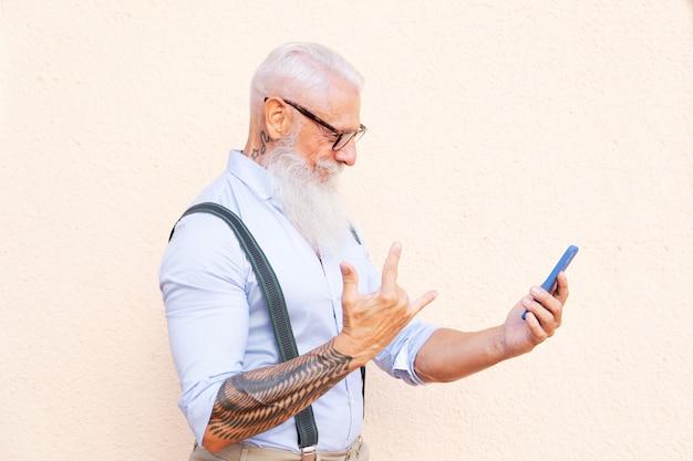 Senior hipster man met tatoo caling en plezier maken met een telefoon, geluk, technologie en ouderen levensstijl mensen concept