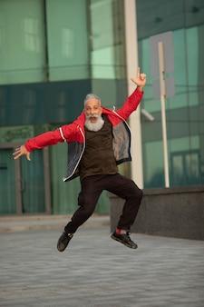 Senior hipster met stijlvolle baard portretten. volwassen man springen op straat.