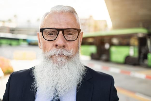 Senior hipster zakenman wachten op busstation - focus op gezicht