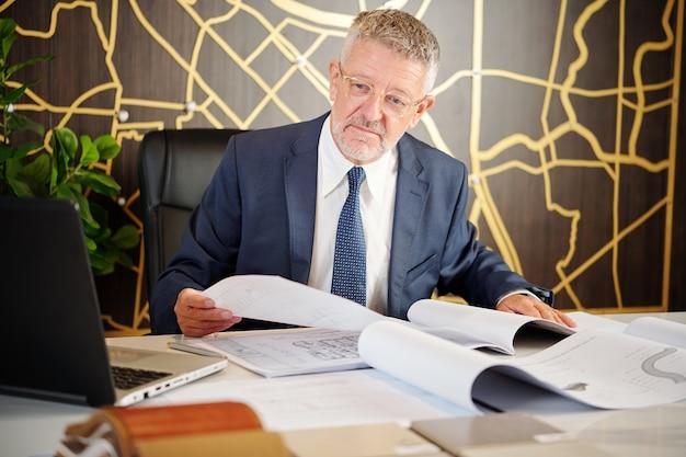 Senior hoofdingenieur of ministerie van bouwvakker die bouwprojectdocumentatie controleert