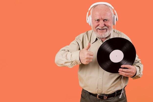 Senior houdt van muziekplaten met kopie-ruimte