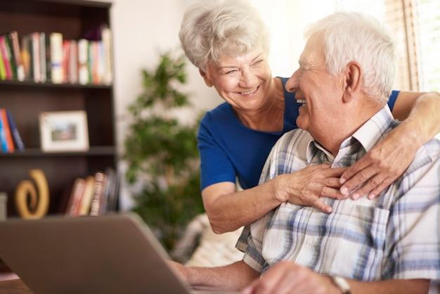 Senior huwelijk met behulp van laptop in de woonkamer