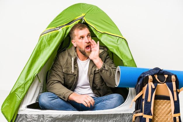 Senior in een tent geïsoleerd op wit schreeuwen en houden palm in de buurt van geopende mond.