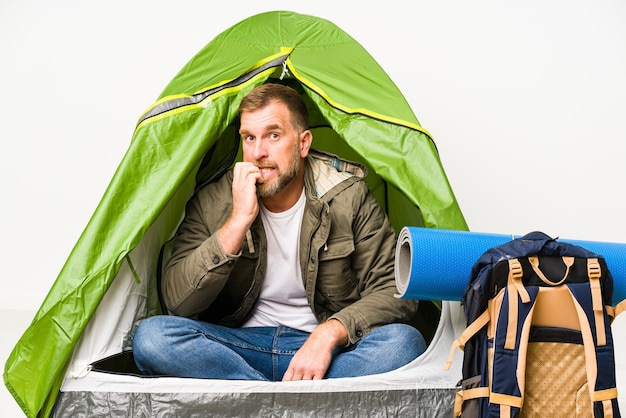Senior in een tent geïsoleerd op wit vingernagels bijten, nerveus en erg angstig.