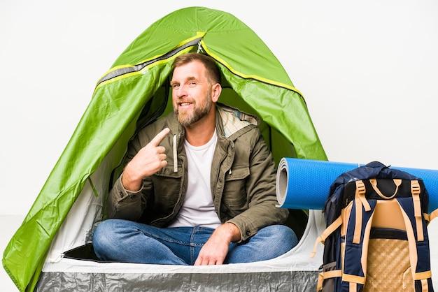 Senior in een tent geïsoleerd op wit wijzend met vinger naar je alsof uitnodigend dichterbij komen.