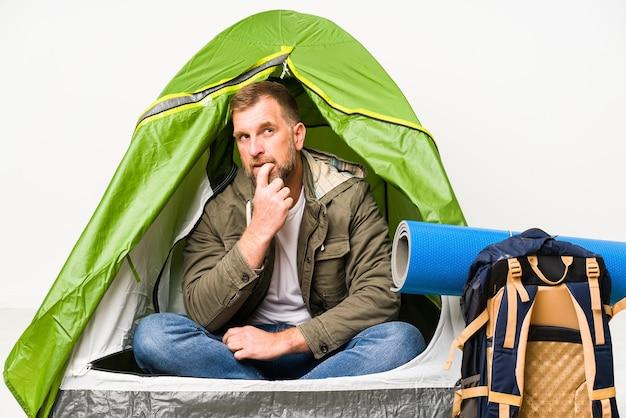 Senior in een tent geïsoleerd op witte achtergrond ontspannen denken over iets kijken naar een kopie ruimte.