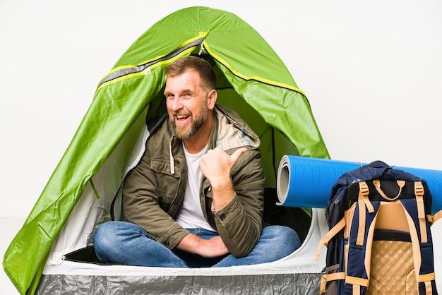 Senior in een tent geïsoleerd op witte punten met duimvinger weg, lachend en zorgeloos.