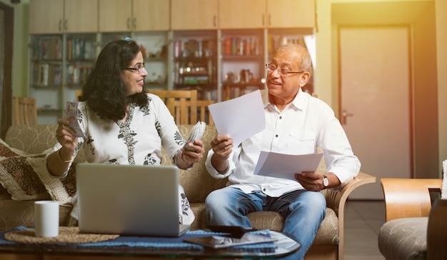 Senior indiase aziatische paar boekhouding, huisfinanciering doen en rekeningen controleren met laptop, rekenmachine en geld ook met spaarvarken zittend op de bank of tafel thuis