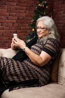 Senior indiase aziatische vrouwen die naar muziek luisteren met een koptelefoon terwijl ze een tabletcomputer vasthouden of telefoneren of praten en thuis op de bank of bank zitten