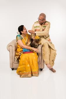 Senior indiase echtpaar in traditionele indiase kleding zittend op de bank en snoep eten