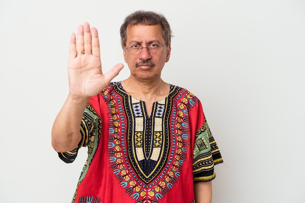Senior indiase man draagt een indiaas kostuum geïsoleerd op een witte achtergrond staande met uitgestrekte hand weergegeven: stopbord, voorkomen dat u.