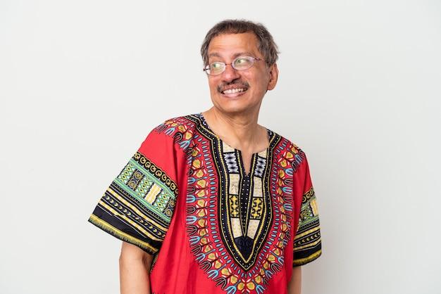 Senior indiase man met een indiaas kostuum geïsoleerd op een witte achtergrond kijkt glimlachend, vrolijk en aangenaam opzij.